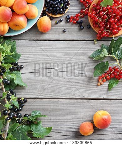 Deluxe berries background. Photography of fresh apricots, bilberry and currants on wooden table. Top view, high resolution product. Harvest concept.