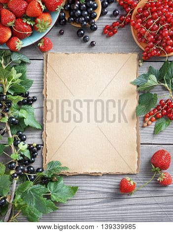 Healthy food background. Open recipe book with Strawberry and currants on wooden table. Copy space, top view, high resolution product.