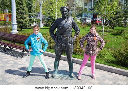 SAMARA, RUSSIA - MAY 8, 2015:Two girls (with model releases) pose near Monument of Sukhov (Character of film White Sun of Desert) at Embankment