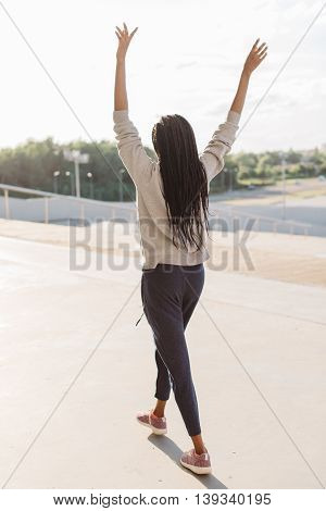 Back side view of happy woman with headphones and raised hands walking outdoor in sunny weather.