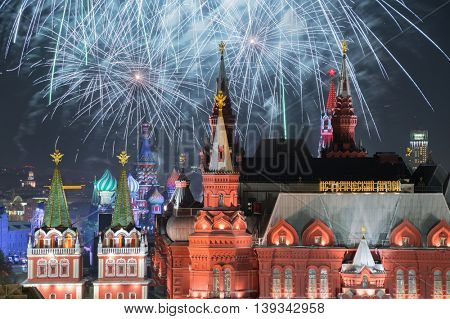 Fireworks explode over Kremlin, St. Basil Cathedral, Historical museum at night on Red Square in Moscow