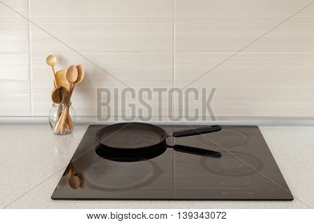 Closeup of pot and wooden spoons in modern kitchen with induction stove