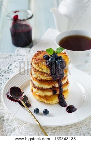 Cottege cheese pancakes Gluten-free with blueberry sauce on a light background. Selective focus.