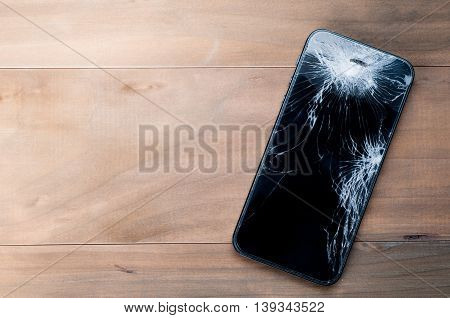Smartphone mobile with a broken screen. Background wood.