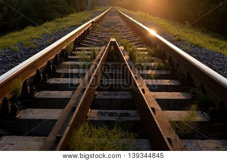 Sunset over the railway, sun glare on the rails