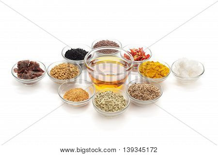 Different types of Indian spices with mustard oil in glass bowl isolated on white background. Elevated view.