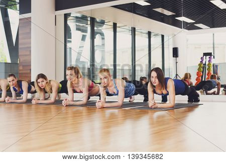 Group of young women in fitness club. Strong sporty girls do plank for abs exercise. Aerobics training, healthy lifestyle.