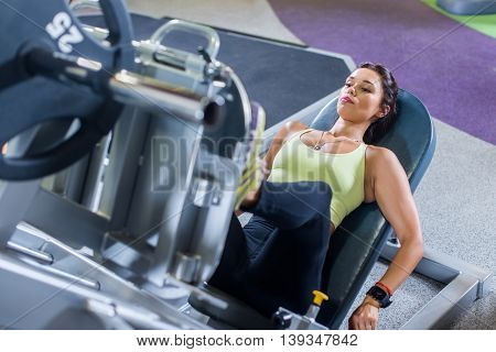 Fit woman working out on leg press machine in gym