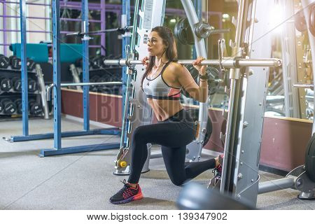 Fit girl doing lunges with the smith machine.