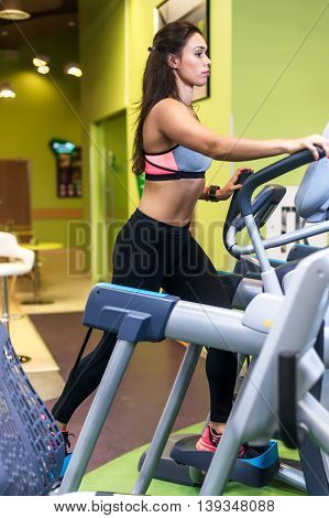 Fit woman doing cardio in an elliptical trainer in a gym
