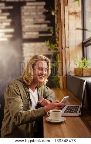 Happy young man sitting at table using mobile phone in cafeteria