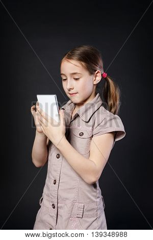 Portrait of serious girl dial on touch screen of mobile phone at black background. Female child using internet in cell phone. New generation devices, communication