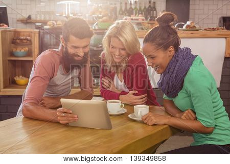 Friends using a tablet in the cafe