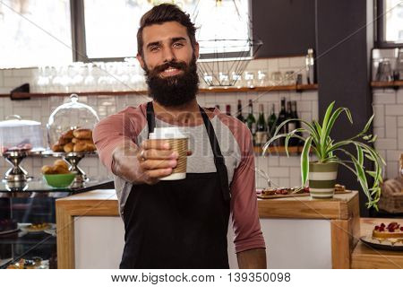 Waiter presenting a disposable cup in the cafe