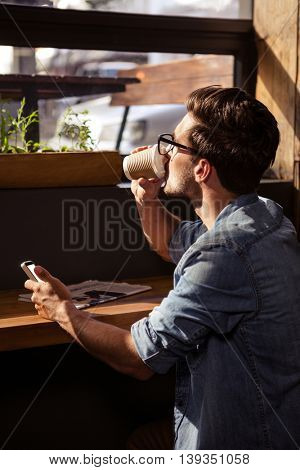 Man drinking coffee and using smartphone in the cafe