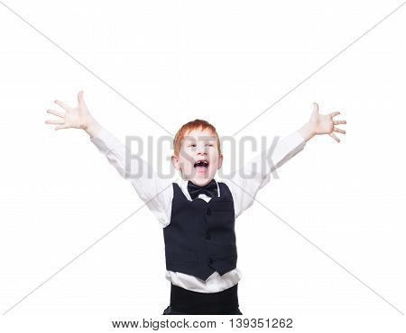 Little cute excited redhead boy in vest with bow tie pose with raised hands. Portrait of well-dressed emotional child, shouting delighted isolated on white background