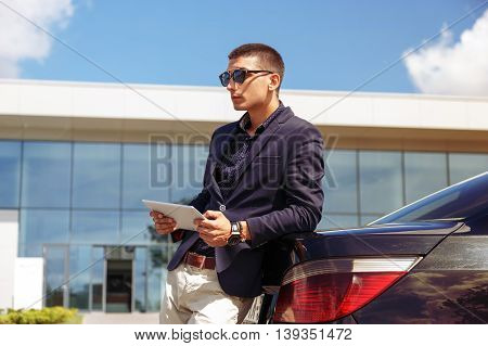 transport, business trip, technology and people concept - close up of young man with tablet pc computer and car outdoors