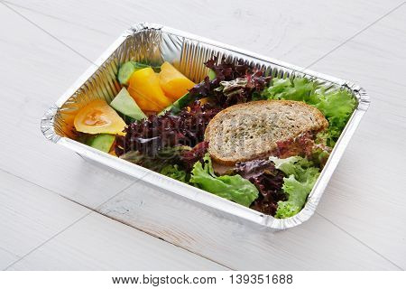 Healthy food delivery and diet concept. Take away of fitness meal. Weight loss lunch in foil boxes. Whole-grain sandwich with boiled beef and fresh vegetables at white wood
