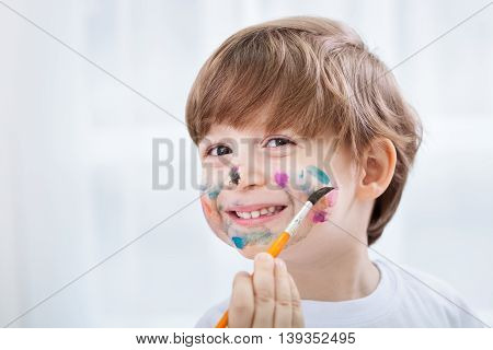 Little Adorable Child Boy Making A Mess With Colors On His Face