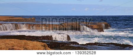 Scene near Maroubra Beach Sydney. Pacific water flowing over rocks.