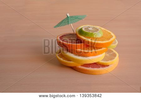 Slices Of Various Citrus Types With A Cocktail Umbrella - Health And Fitness Concept