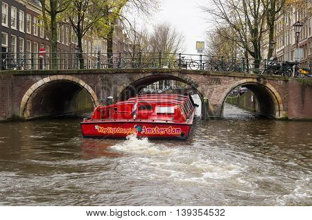 AMSTERDAM NETHERLANDS - NOVEMBER 15 2015: Red sightseeing boat sailing through the amsterdam canals. The city counts 165 canals.
