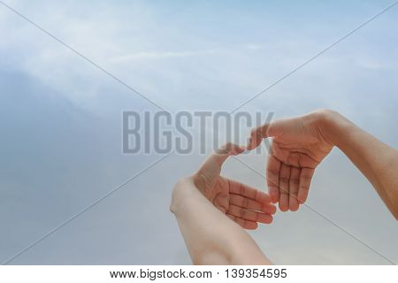 Beautiful woman hands making a heart shape on blue sky background