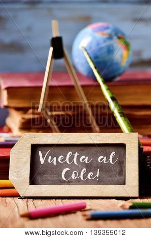 label-shaped chalkboard with the text vuelta al cole, back to school in spanish, some old books and old stationery such as a pen nib or pencils crayons of different colors, on a rustic wooden surface