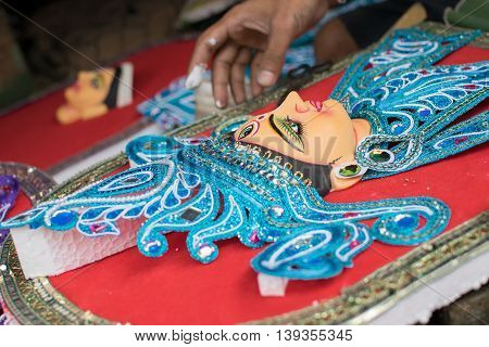 KOLKATA WEST BENGAL INDIA - 13 SEPTEMBER 2015: An unidentified artist preparing clay idol of Goddess Durga as preparation for