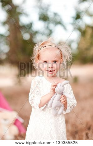 Smiling baby girl 1-2 year old holding toy rabbit outdoors. Looking at camera. Childhood. Happiness.