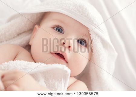 Baby With Blus Eyes Under The White Towel