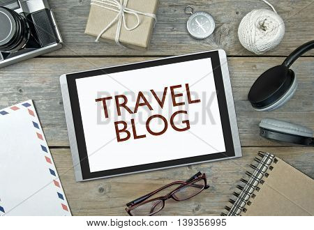 Travel blog digital tablet with stationery objects compass and camera