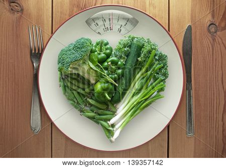 Plate with weighing scales packed with vegtables in a heart shape