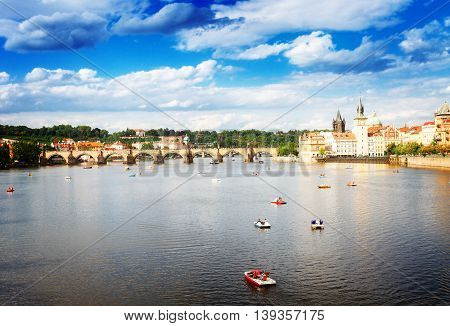 Charles bridge over river Vltava at summer cloudy day, Prague, Chech Republic, toned