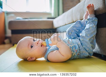 baby lying on the floor with his feet up and drinking watter from a bottle