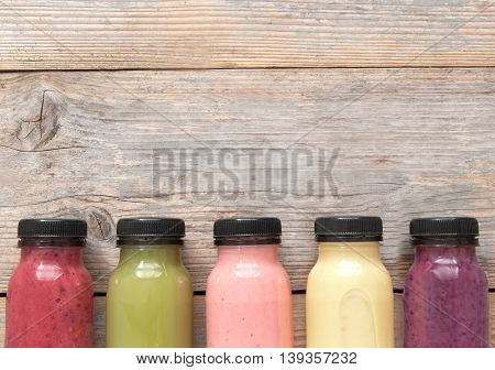 Assorted flavoured smoothie juices in bottles over a wooden background