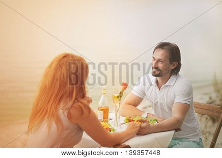 Toned picture of happy beautiful couple spending sunny day in restaurant or cafe. Beautiful beople holding hands and looking at each other and smiling.