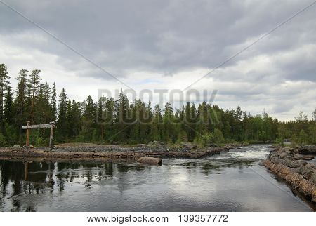 Swedish River In Haelsingland With Wood Sign