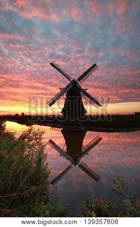 windmill and dramatic sunrise sky reflected in river Holland