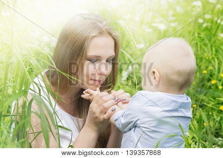 Happy mother with her son in a meadow lit by the morning sunlight