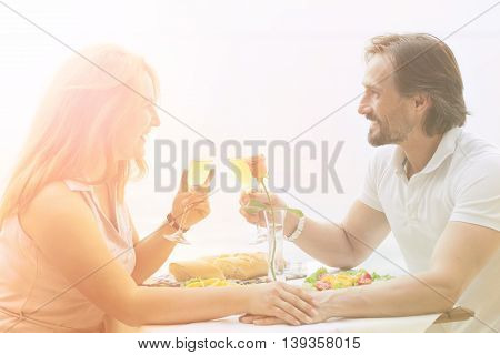 Dating concept. Happy middleaged man and woman having date in restaurant or cafe by sea. Beautiful people sitting face to face, holding glasses with wine.