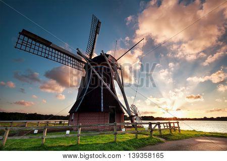 charming Dutch windmill by lake at sunset Netherlands