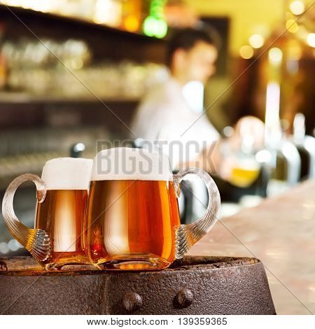 Two glasses of beer on the wooden barrel in the bar
