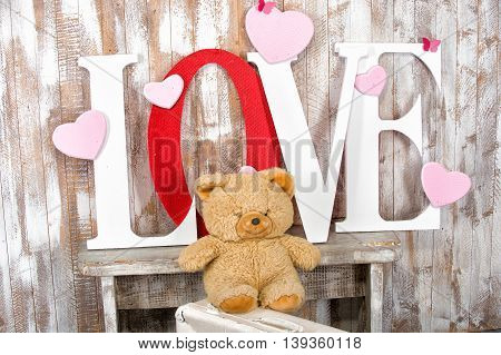 handmade letters with love word text red and white color near bear toy hearts and butterfly on wooden wall background as wedding or valentines day decoration