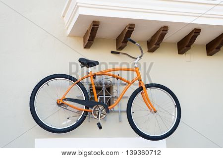 orange sport bicycle with iron hull and rubber tyre wheels hanging on white wall sunny day outdoor with nobody
