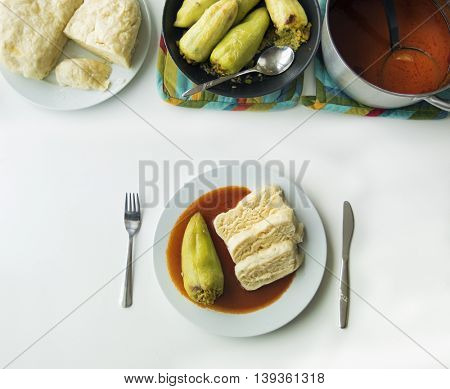 Green Peppers stuffed with spelt hails and meat with homemade dumplings and tomato sauce. Flat lay food on white wooden table.