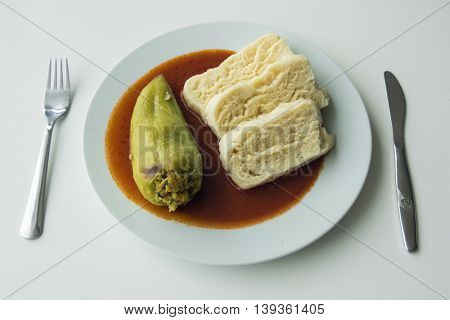 Stuffed green peppers with homemade dumplings and tomato sauce. Served food on white plate with fork and knife.