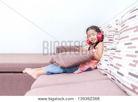 Portrait of cute asian Thai little girl using mobile phone and red headphone with copy space