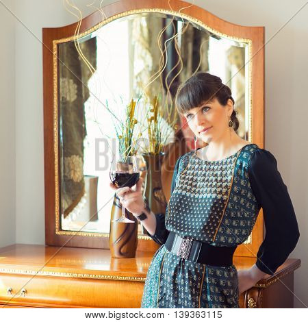 Portrait of a young beautiful fashionable woman in interior with a glass of wine near the mirror