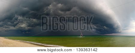 Storm and windsurfer. Approaching storm and floating away sail boat